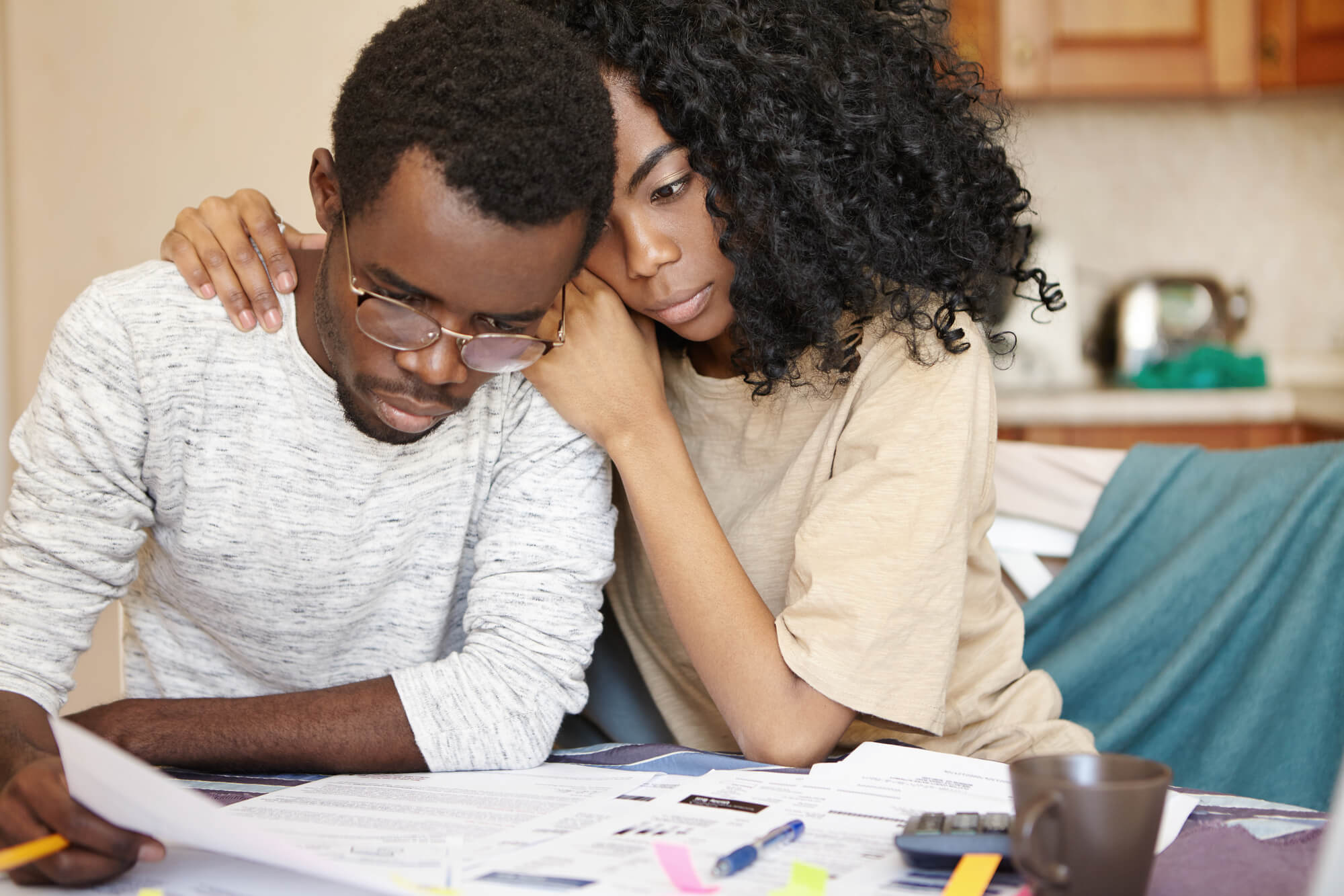 """""""Man Calculating family budget"""" - Wife hugging man at table"""