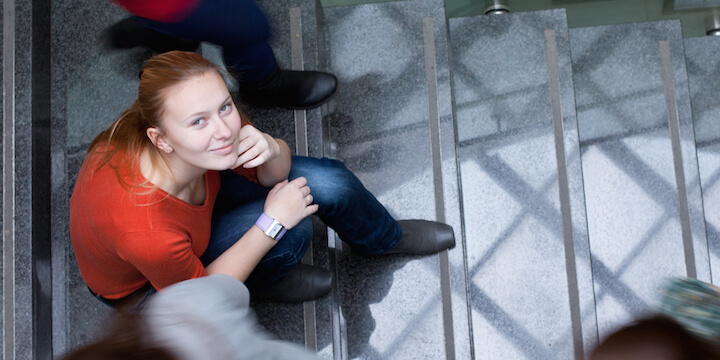 Girl student looking upwards while sitting down on stairs