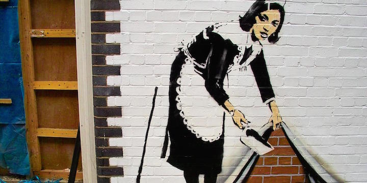 street art of maid lifting drapes and sweeping
